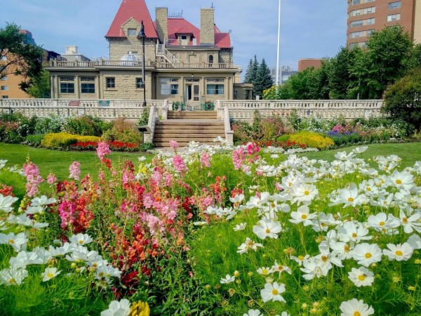 Image of garden with pink and white flowers in the foreground, with sandstone mansion with red roof in background.