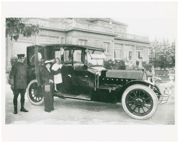 Black and white image circa 1911 of woman with young daughter and their chauffeur standing beside a car with sandstone mansion in the background.