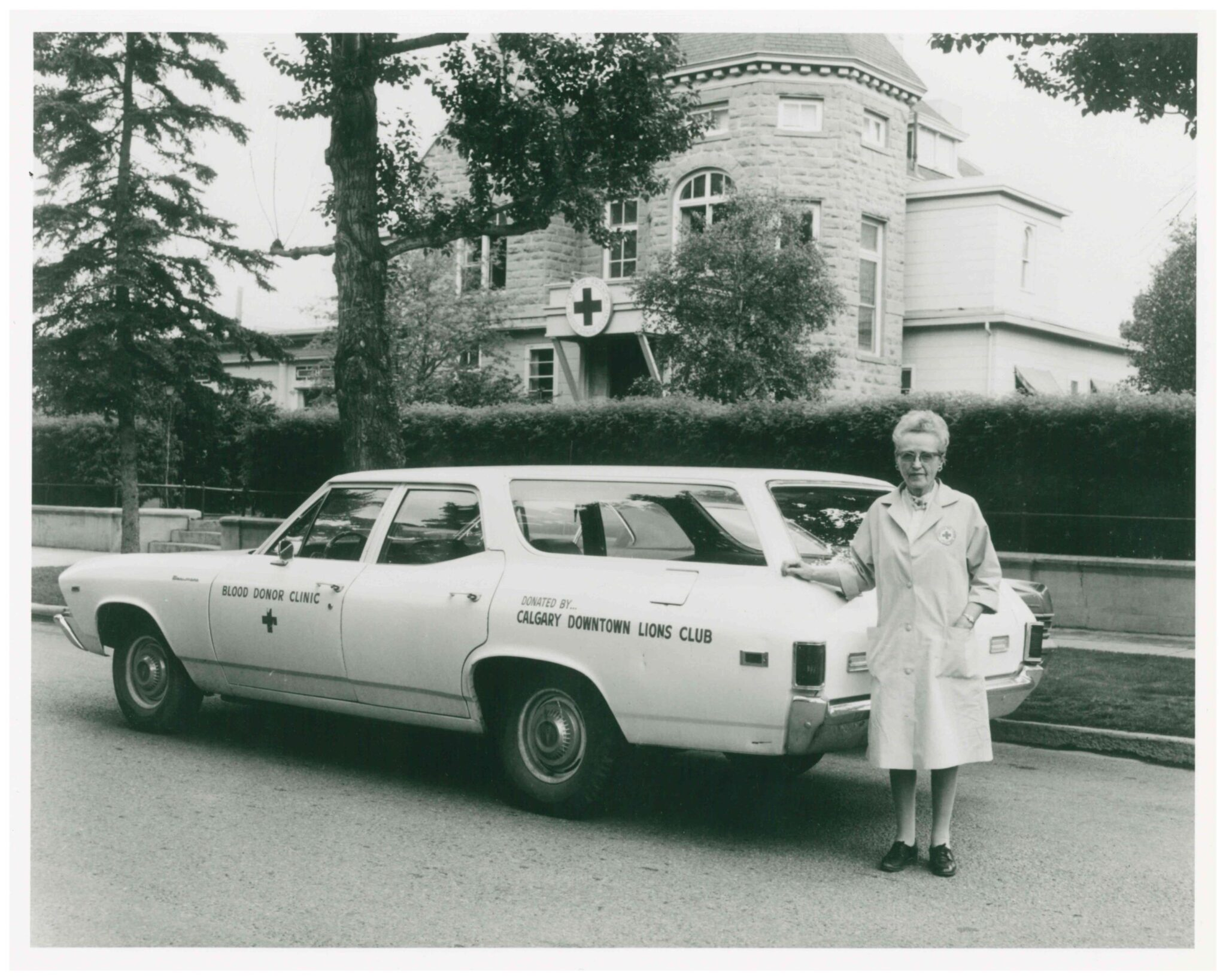 Black and white image of women in white medical coat standing beside white car in front of a sandstone building that houses the blood donor clinic.