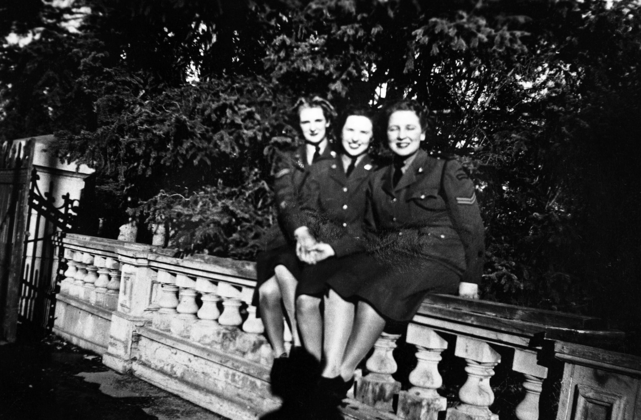 Black and white image circa 1944-46 of three women in military uniform sitting on balustrade in front of group of trees.