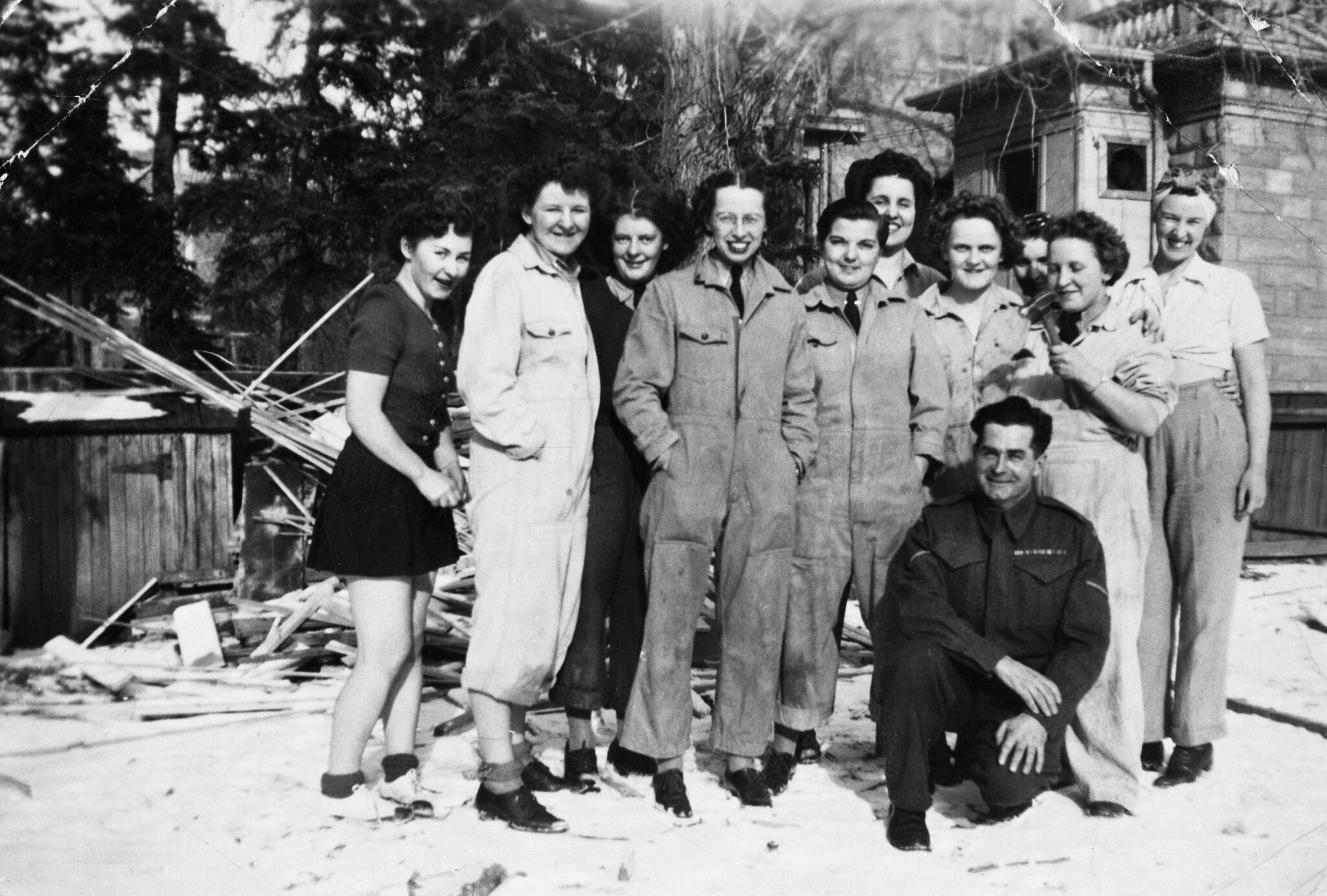 Group picture of ten women and one man in yard of sandstone building in winter. Some women are wearing coveralls. Circa 1944-46.
