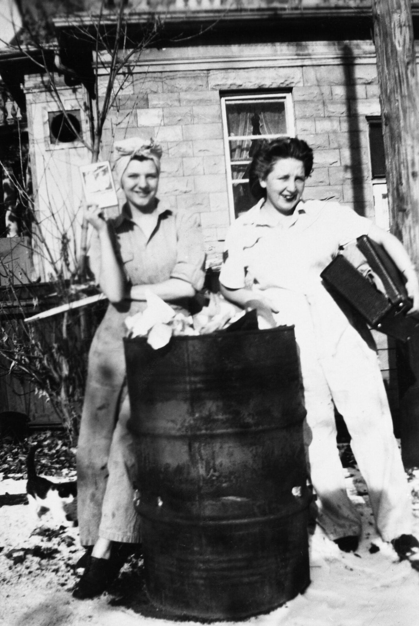 Black and white image of two women in coveralls outside sandstone building beside metal barrel circa 1944-46