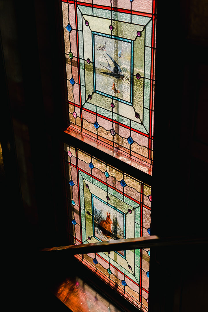 Multi-coloured stained glass window inside stairwell, featuring central images of birds and a rabbit.