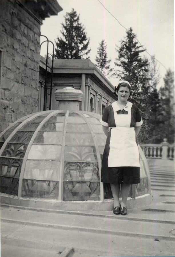 Woman in maid's uniform standing next to stained glass dome window on roof.