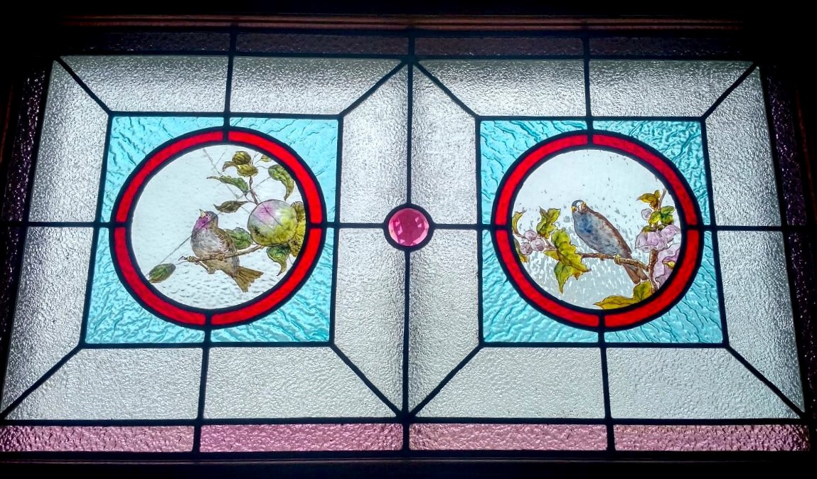 Close up shot of red, blue, purple, and pink stained glass window, with two circular handpainted images of birds.