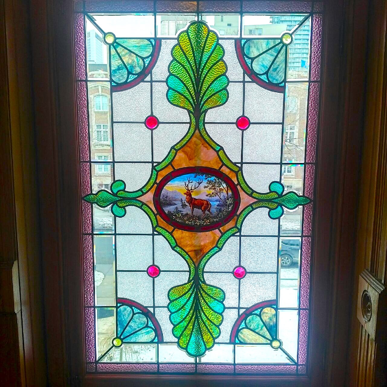 Green, red, brown, and white stained glass window with hand painted image of an elk or male deer in centre.