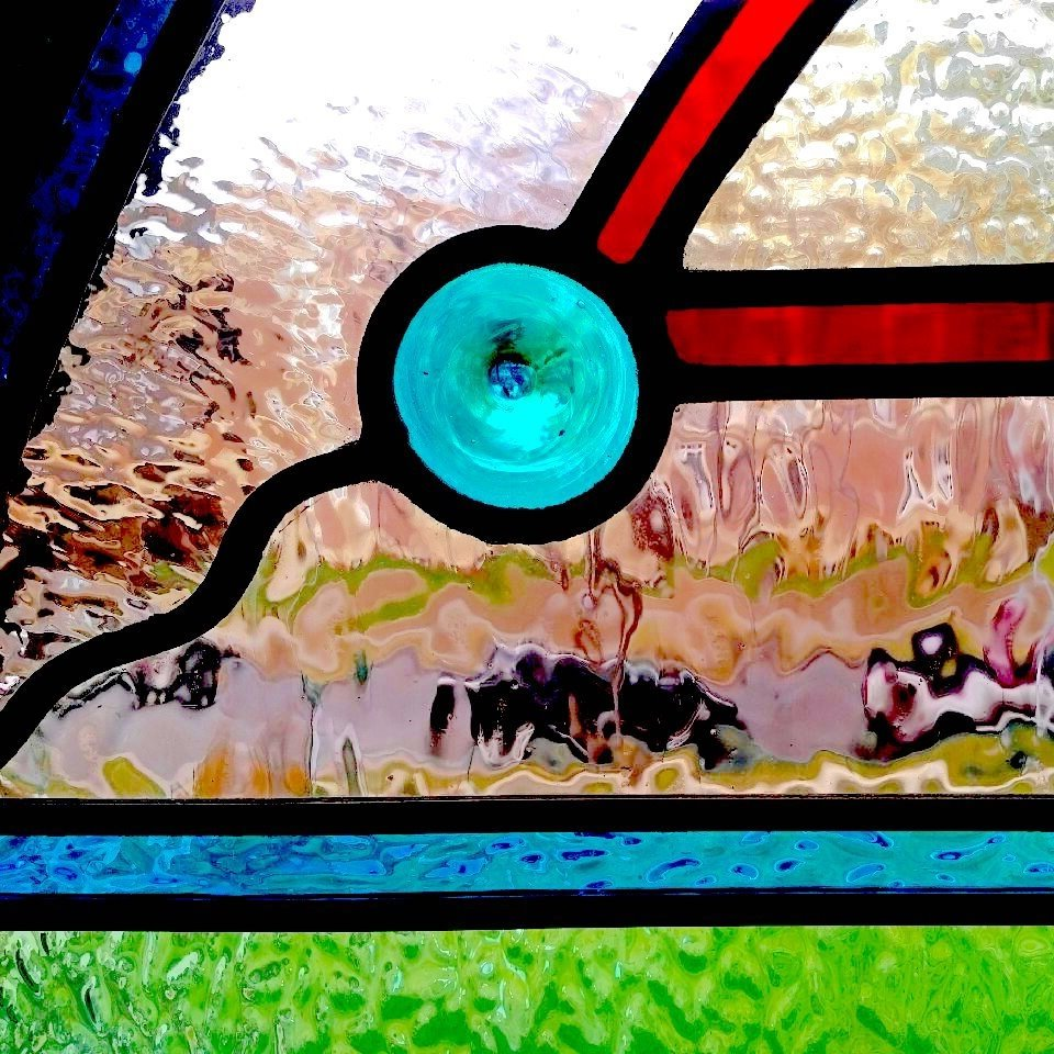 Close up image of abstract blue, red, and green stained glass.