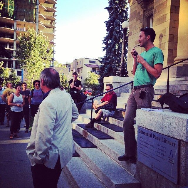 Man with microphone standing on library steps outside, giving a walking tour to a group of people.