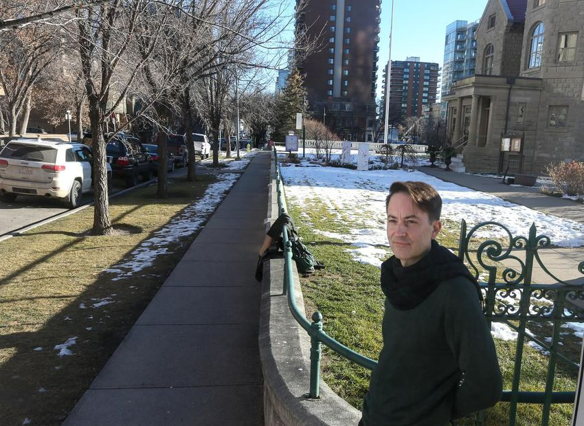 Man leaning up against green rail in front of sandstone mansion