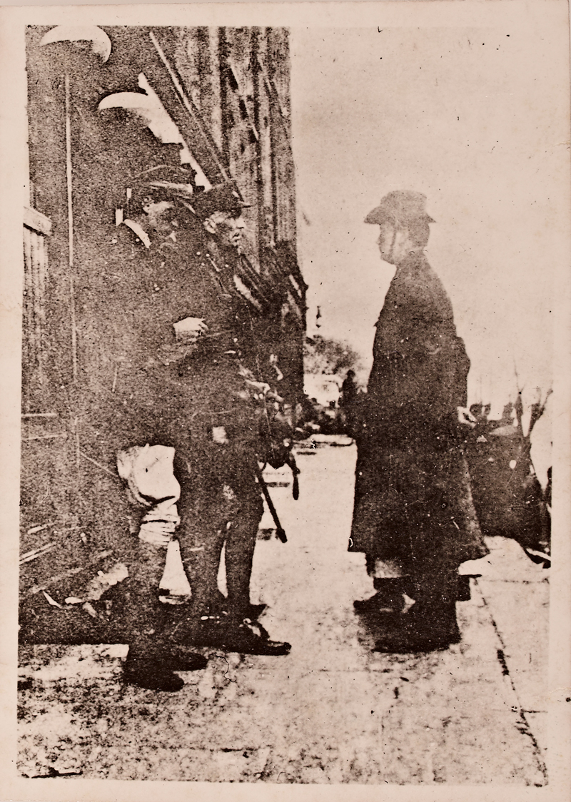Poor photo of three men, two in uniform and one delivering a note of surrender. There is a woman behind the third man, but only her feet and skirts are visible.