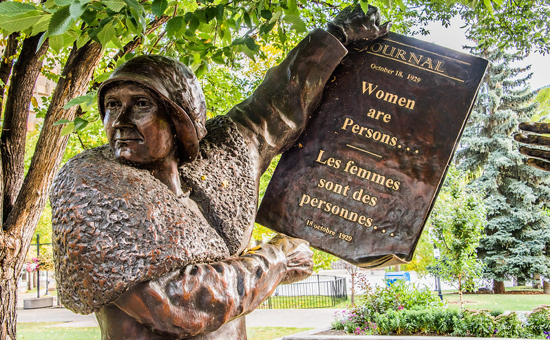 """Close up shot of a bronze statue of a woman holding a paper that reads """"Women are persons"""" from October 18, 1929."""