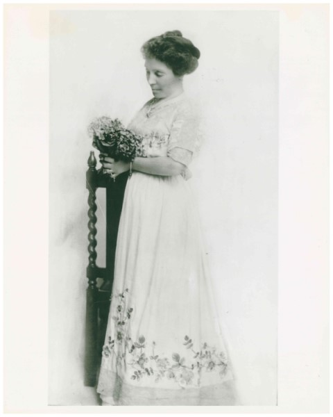 Black and white studio portrait of woman wearing white dress and holding flowers.