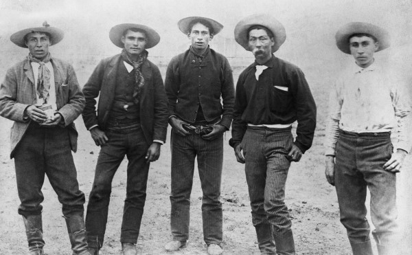 Black and white image of a group of five Metis men standing outside.