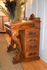Side view of a dark wood Davenport desk. The top of the desk is slanted and on the side are four drawers.
