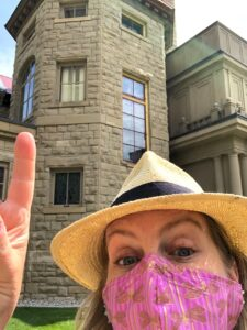 Woman wearing a yellow hat and pink face mask pointing at a sandstone building.